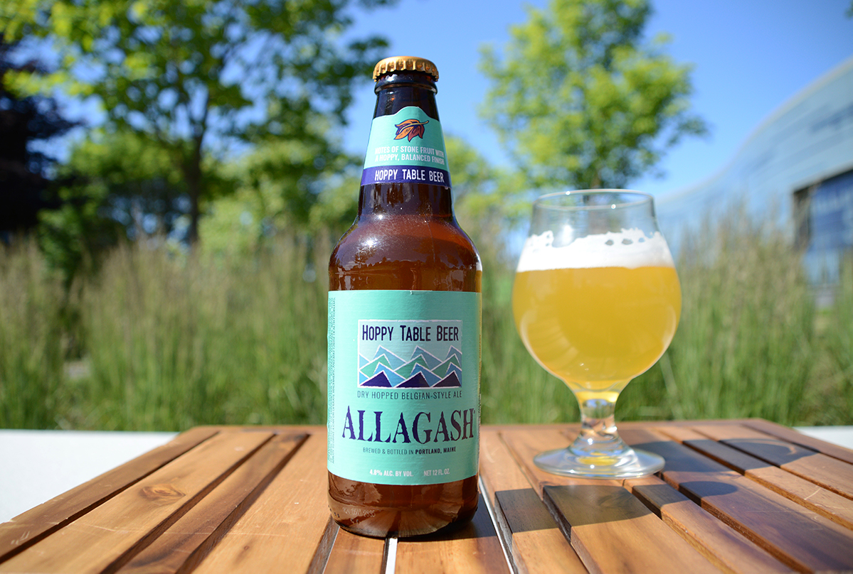 Allagash beer bottle next to a glass of beer