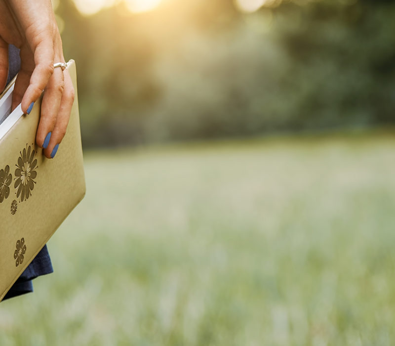 woman holding a book in a field
