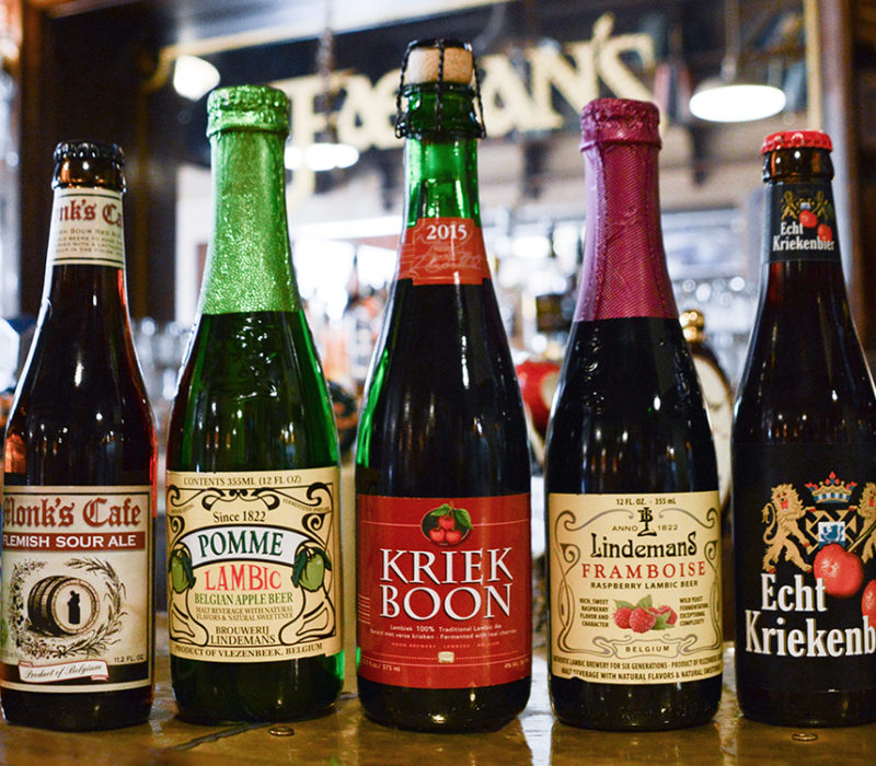 7 lambic beer bottles on a bar